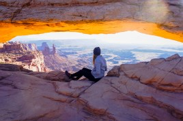 Moab Arch in Canyonlands National Park. Sunrise photography with Sierra of Somewhere Sierra sitting in the middle of the arch.