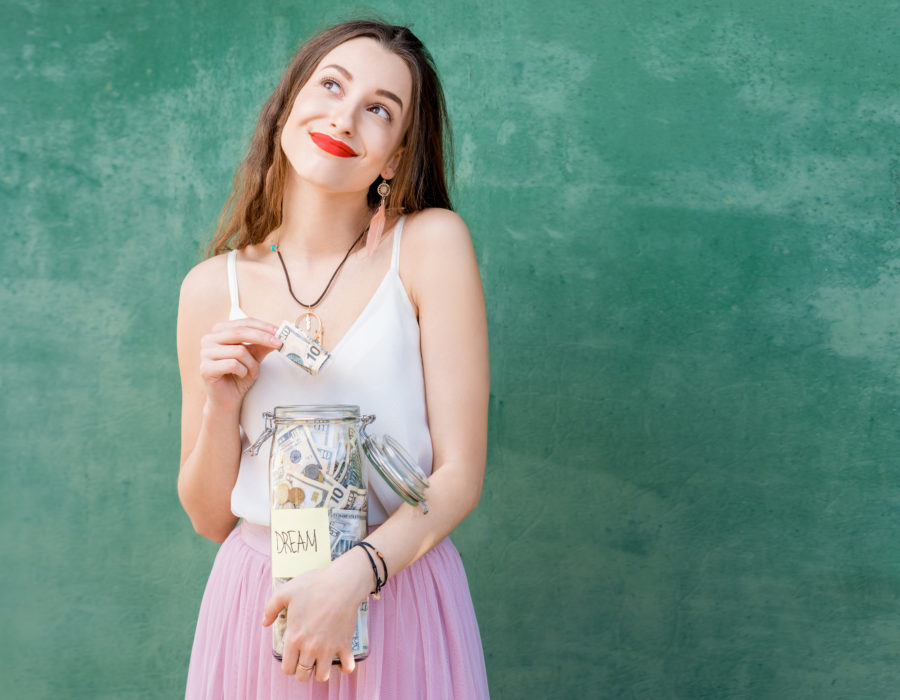 Beautiful young woman holding a bottle with money savings for the dream standing on the green background. Savings for the future concept