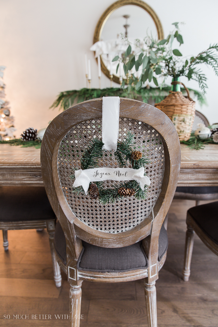 Wooden chairs with evergreen wreath on it hanging by a white ribbon and Joeux Noel on the ribbon.