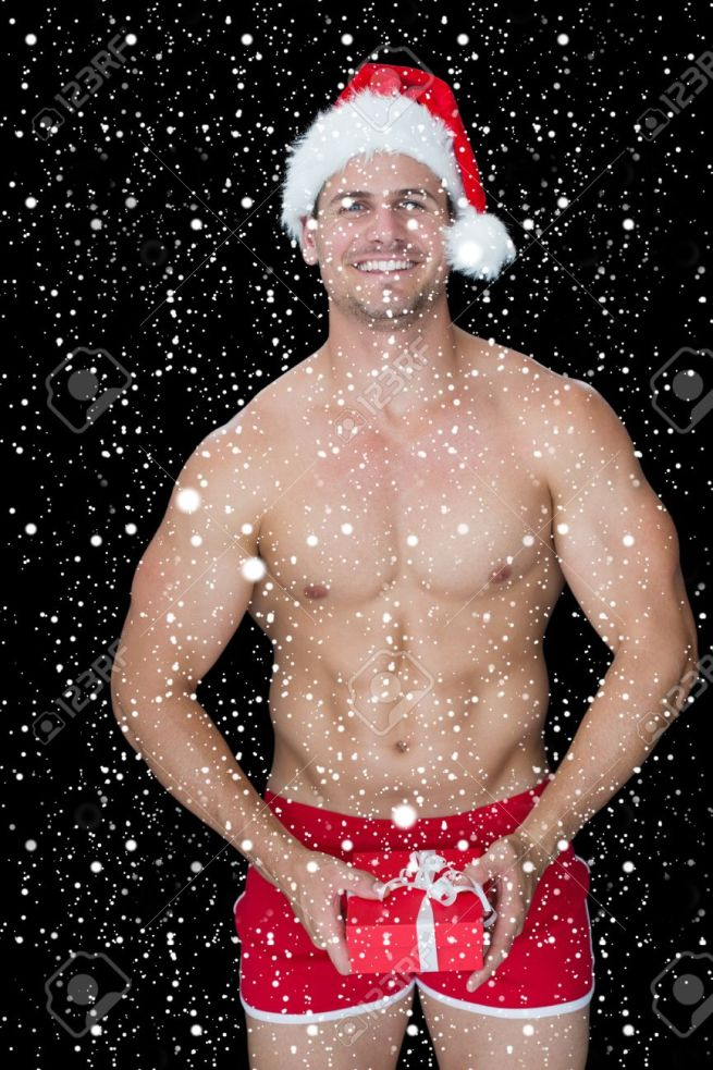 Smiling muscular man posing in sexy santa outfit holding gift against snow falling