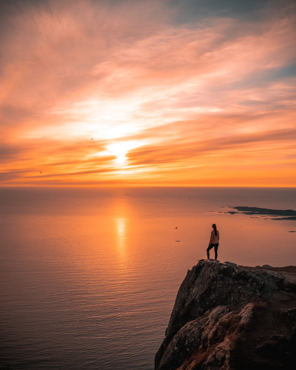a person standing on a cliff overlooking the sea during golden hour