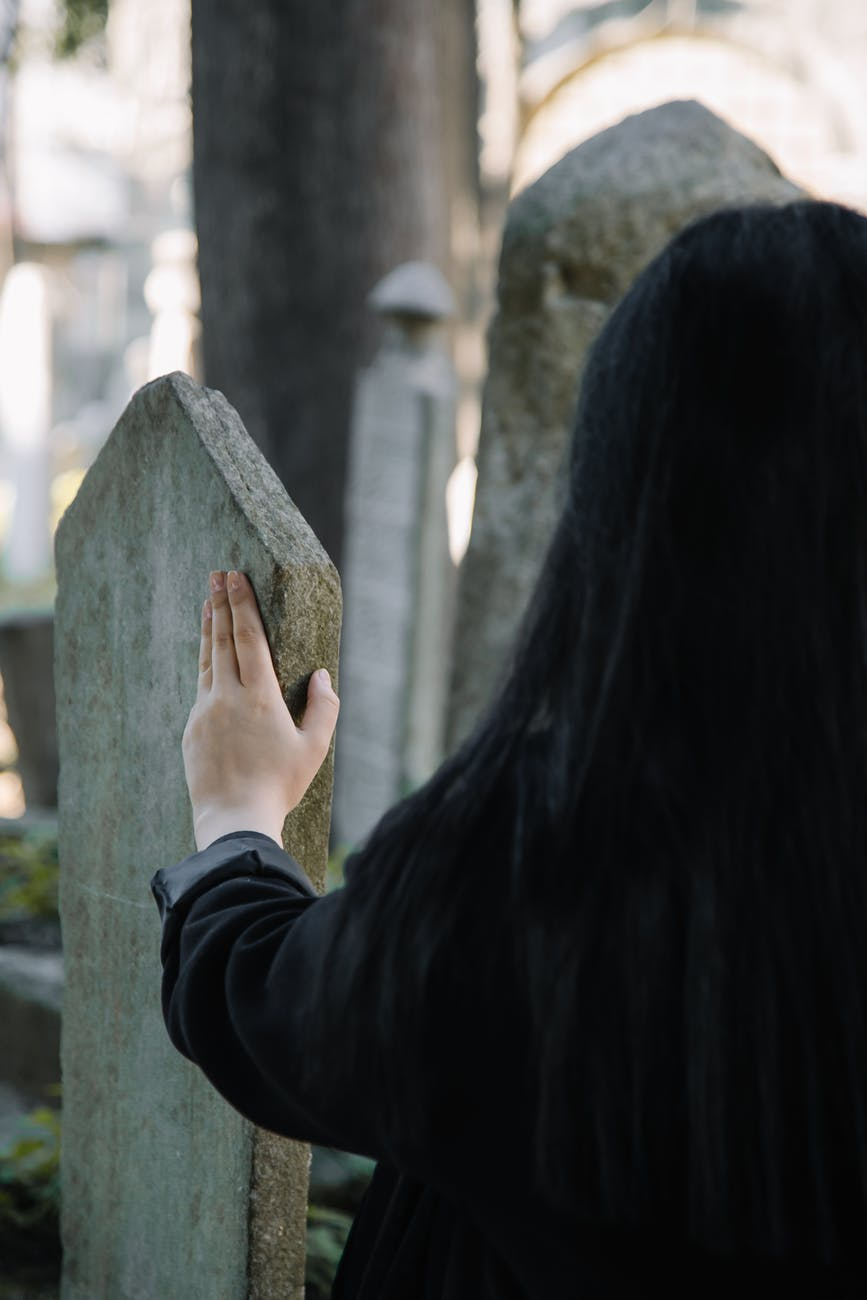anonymous woman touching shabby tombstone