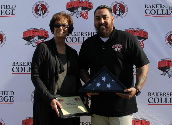 KCCD Board of Trustees member Kay Meek presents a ceremonial American flag to BC Veterans advisor Armando Trujillo.