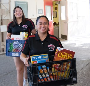 two students delivering food to the pantry