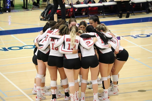 Renegades Women Volleyball team in huddle