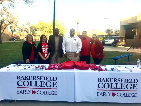 BC Staff at Bakersfield College Early College tables of bags, laniards, folders and giveaways at Shafter High.