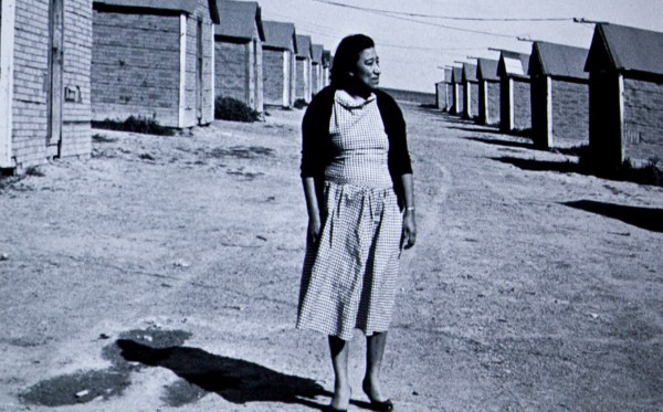 Moreno standing in a dirt lane between bunk houses, black & white picture.