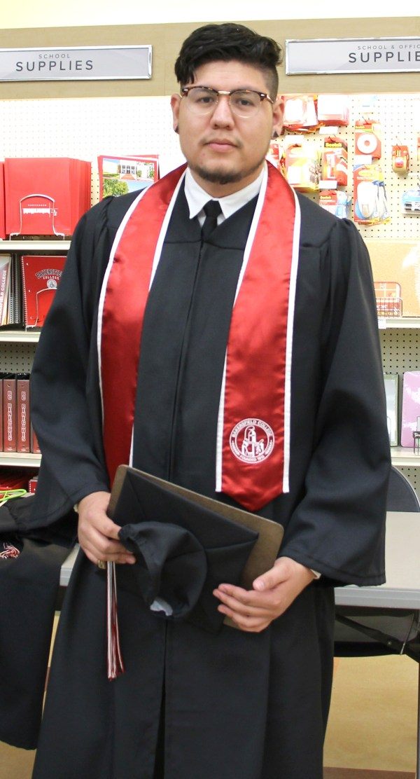 Male graduate in gown holding cap