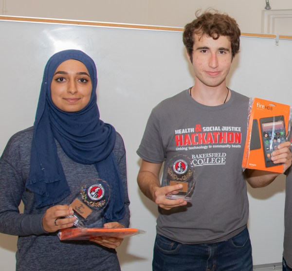 Two Hackathon students holding trophies