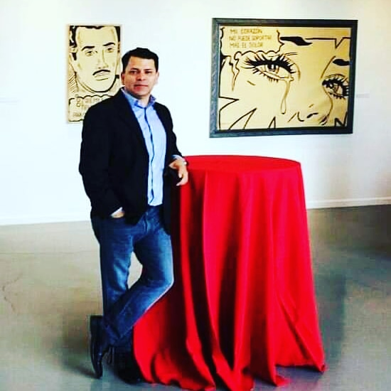 Standing at a table in front of graphic drawing of man and graphic drawing of woman crying.