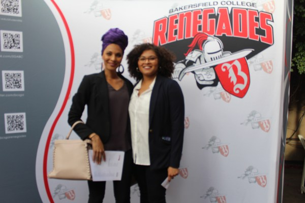 2 females in front of the Renegade logo backdrop.
