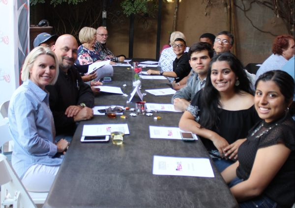Table filled with smiling people.