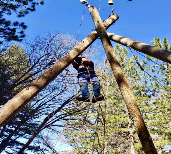 Standing in rope ladder between poles.