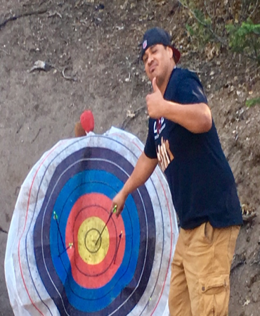 Student with thumb up pulls arrow from center of target.