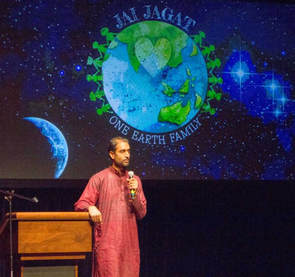 Man speaks in front of Jai Jagat One Earth Family background.