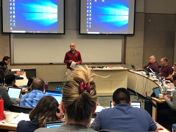 Dean Mourtzanos speaks in front of audience.