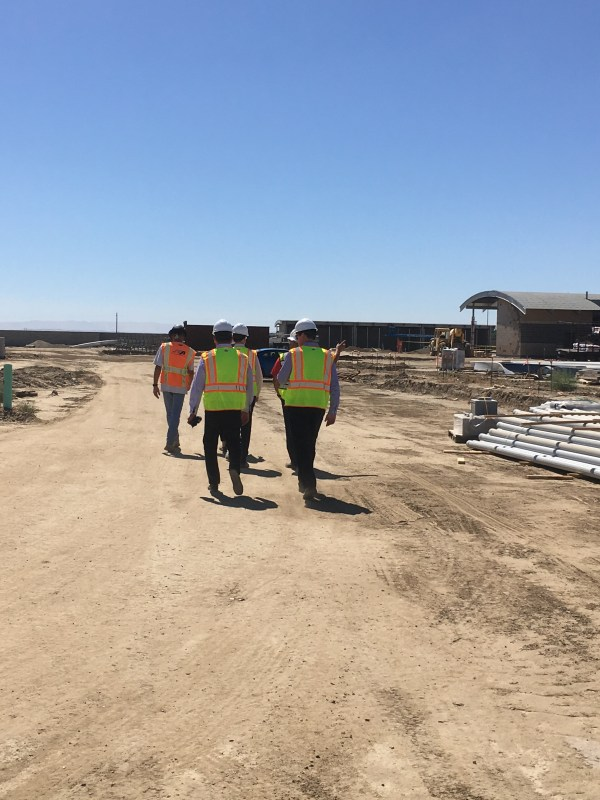 Workers in yellow vests and hard hats walking the dirt road of the construction site.