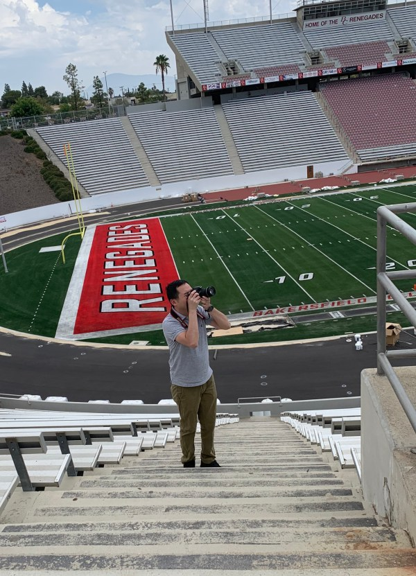 Dylan taking a photo with the stadium field in the background.
