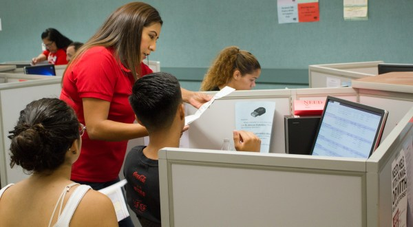 Josie assisting a a student with a form.