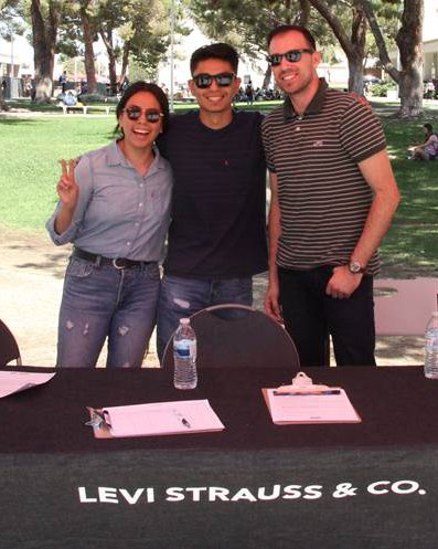 Three Levi Strauss reps standing behind table
