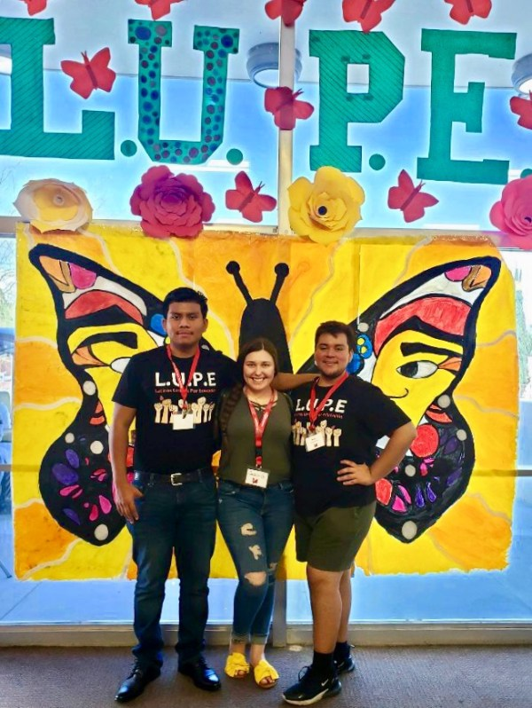 3 students pose in front of the LUPE butterfly backdrop.