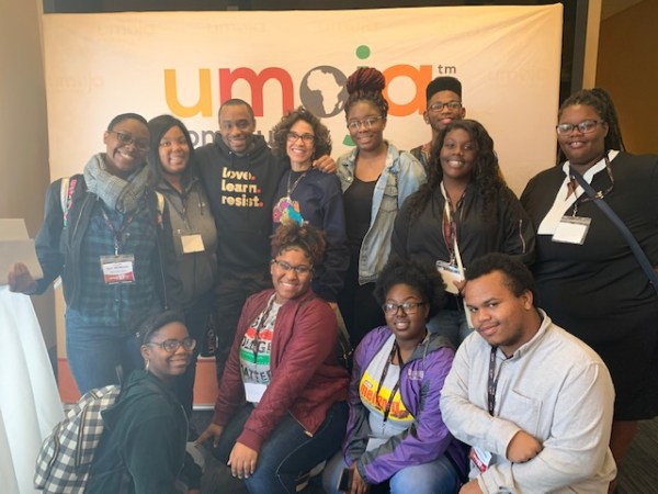 Student with Paula in front of the Umoja sign.