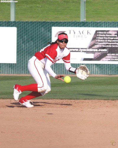 Female player catching softball.