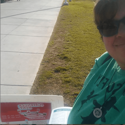 Student selfie with scavenger hunt sign on grass.