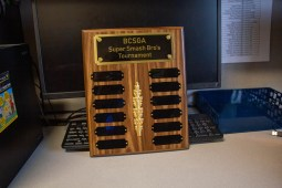 BCSGA Super Smash Bro's Tournament plaque in front of computer.