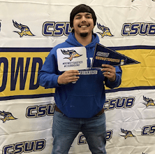 Student with CSUB sign and pendant.