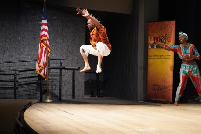 Dancer jumps about 3 feet above stage.