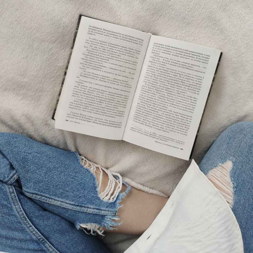 crop unrecognizable woman reading book on soft bed