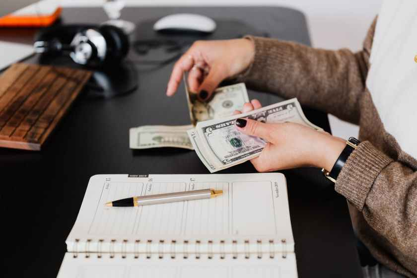 crop businesswoman counting money while sitting at desk