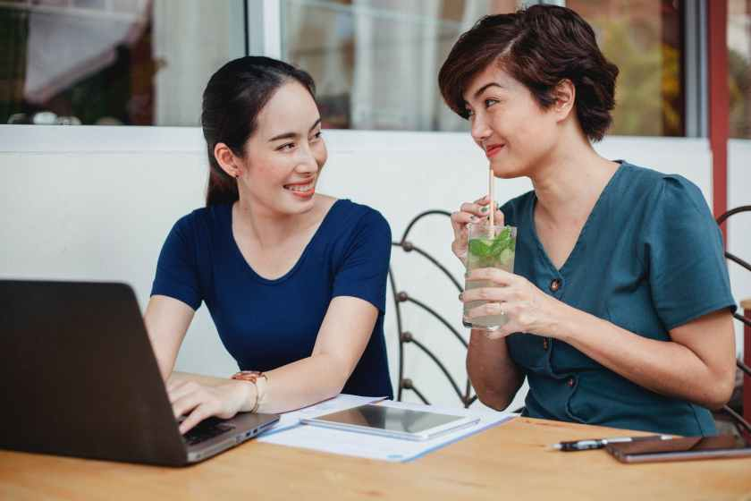 happy asian woman drinking cocktail while working with colleague