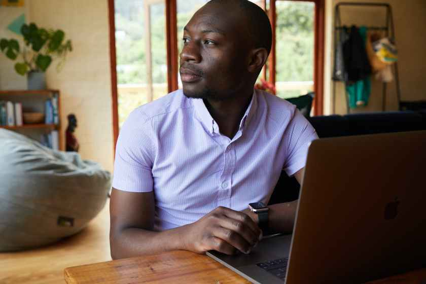 focused black man with laptop at table