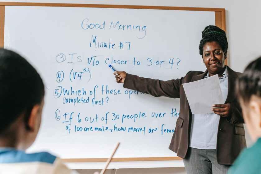 positive black teacher pointing at tasks on whiteboard
