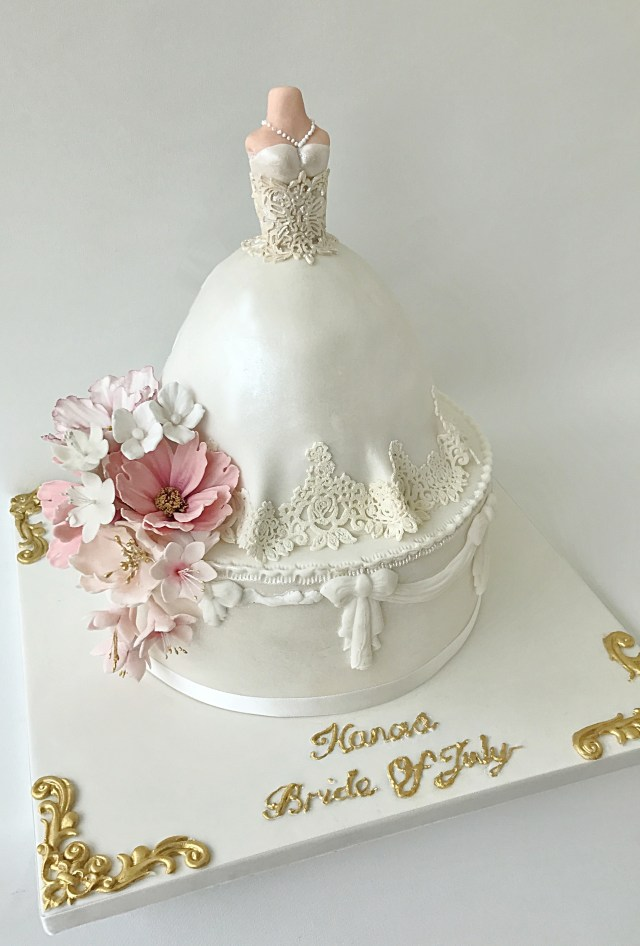 Two tier bridal shower cake with round bottom tier and wedding dress shaped top tier decorated with pink flowers and lace