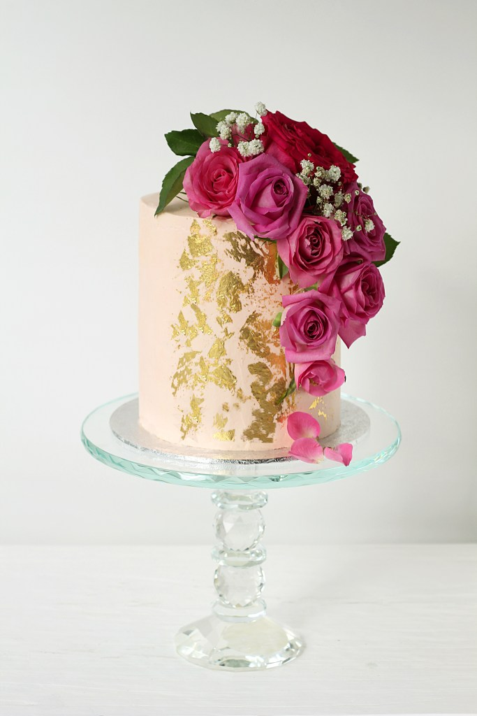 single tier pale pink butter cream celebration cake with a cascade of dark pink roses and flecks of edible gold