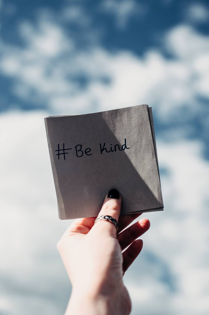 person holding note with be kind text