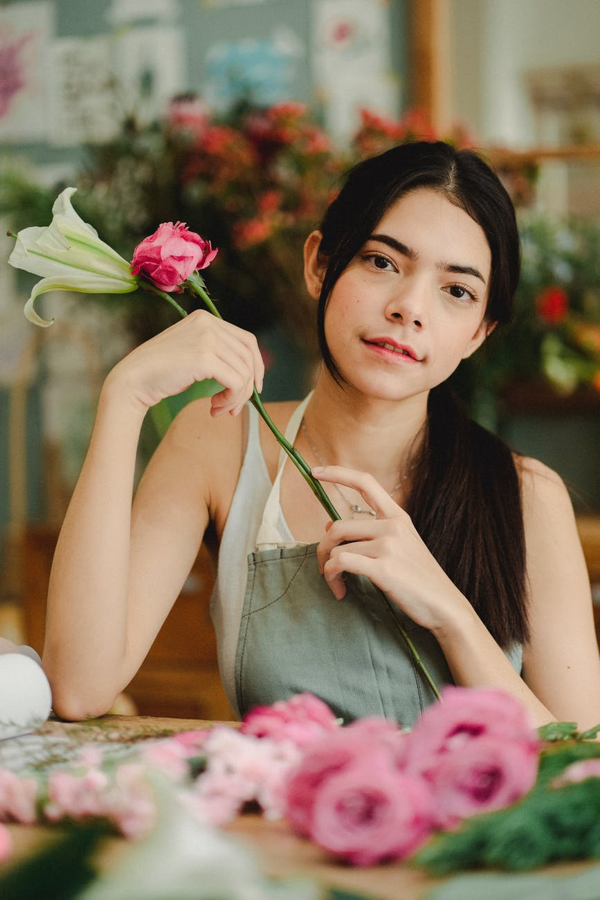 young woman sitting at table with flowers in florist shop