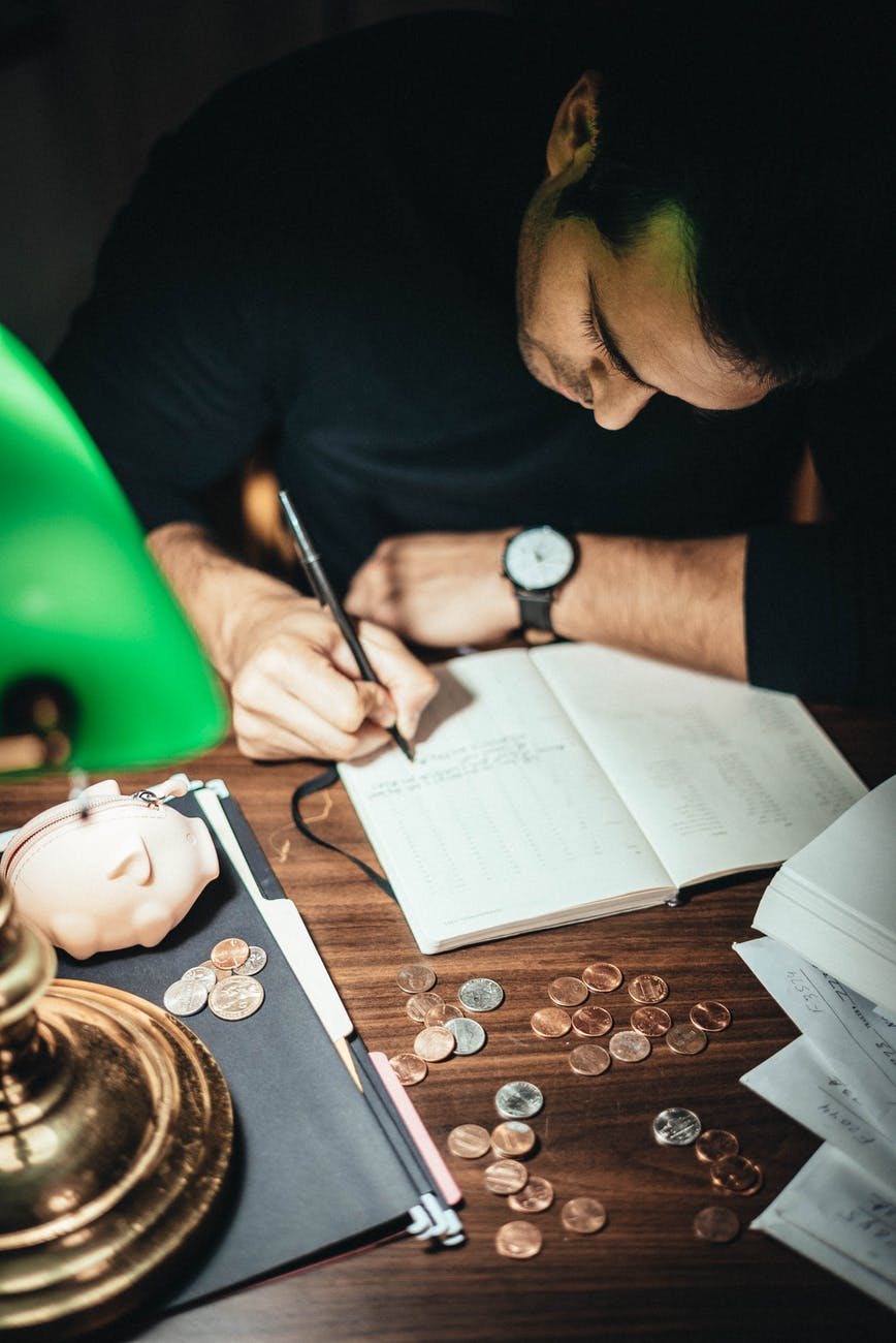 crop accountant taking notes at desk with scattered coins