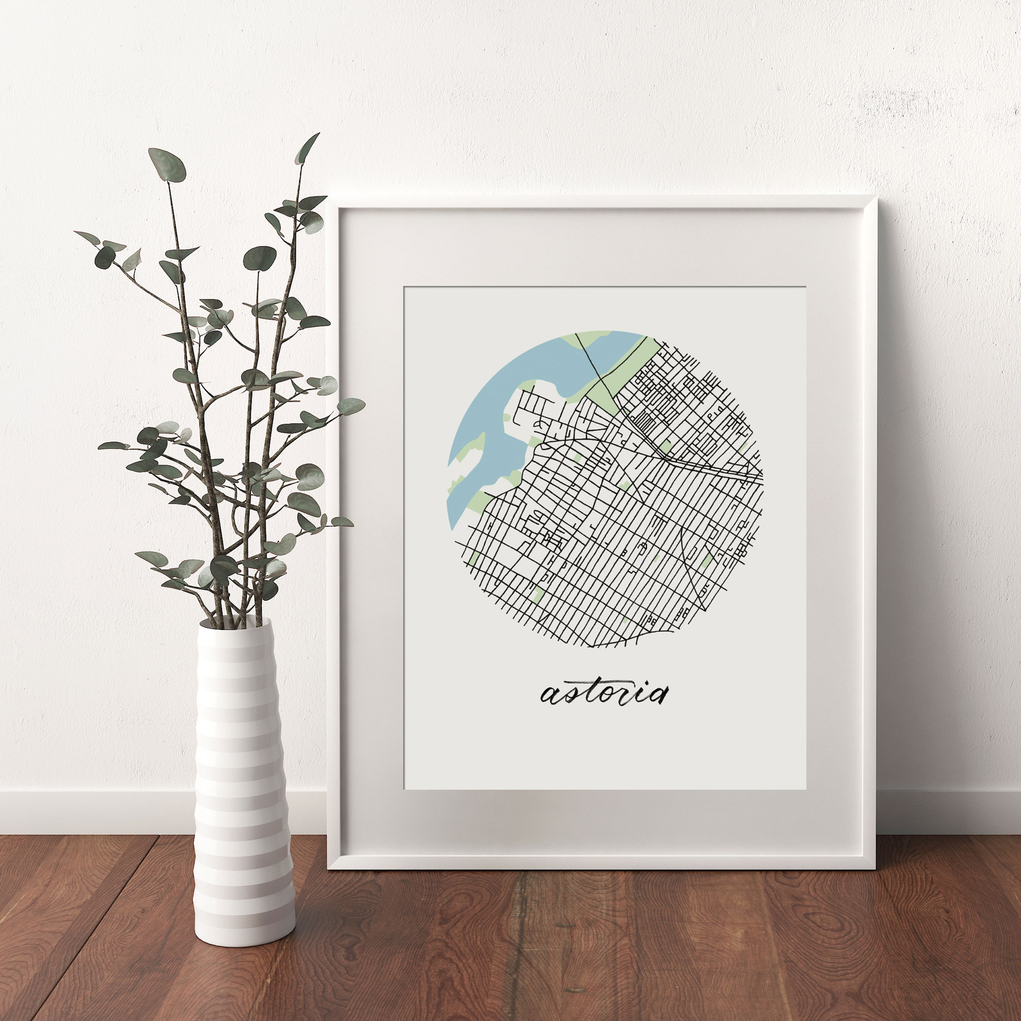 Astoria, Queens Map print framed and leaning on white wall next to dried leaves in a vase