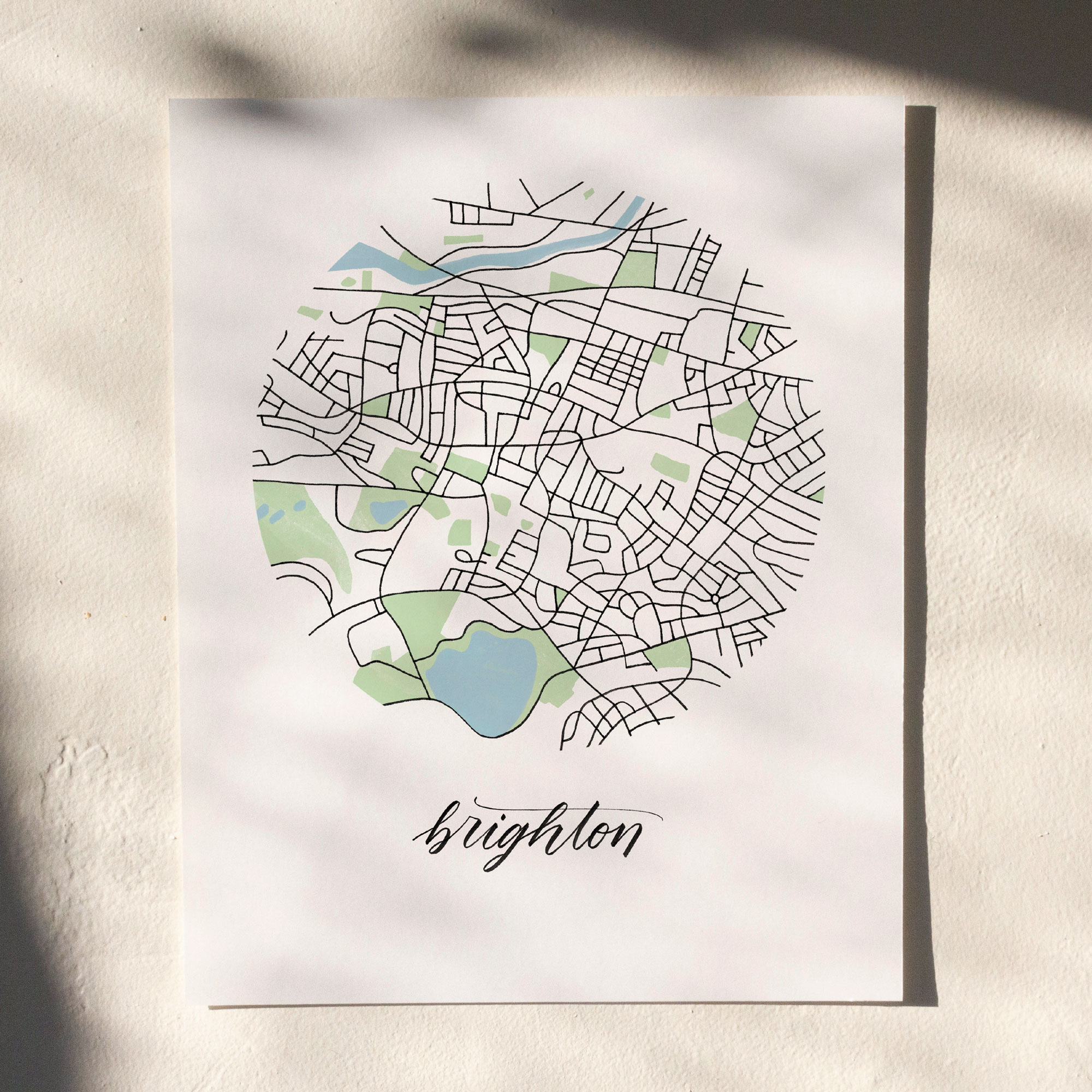 Brighton, Boston Map Print hanging on white wall with leaf shadows across the image