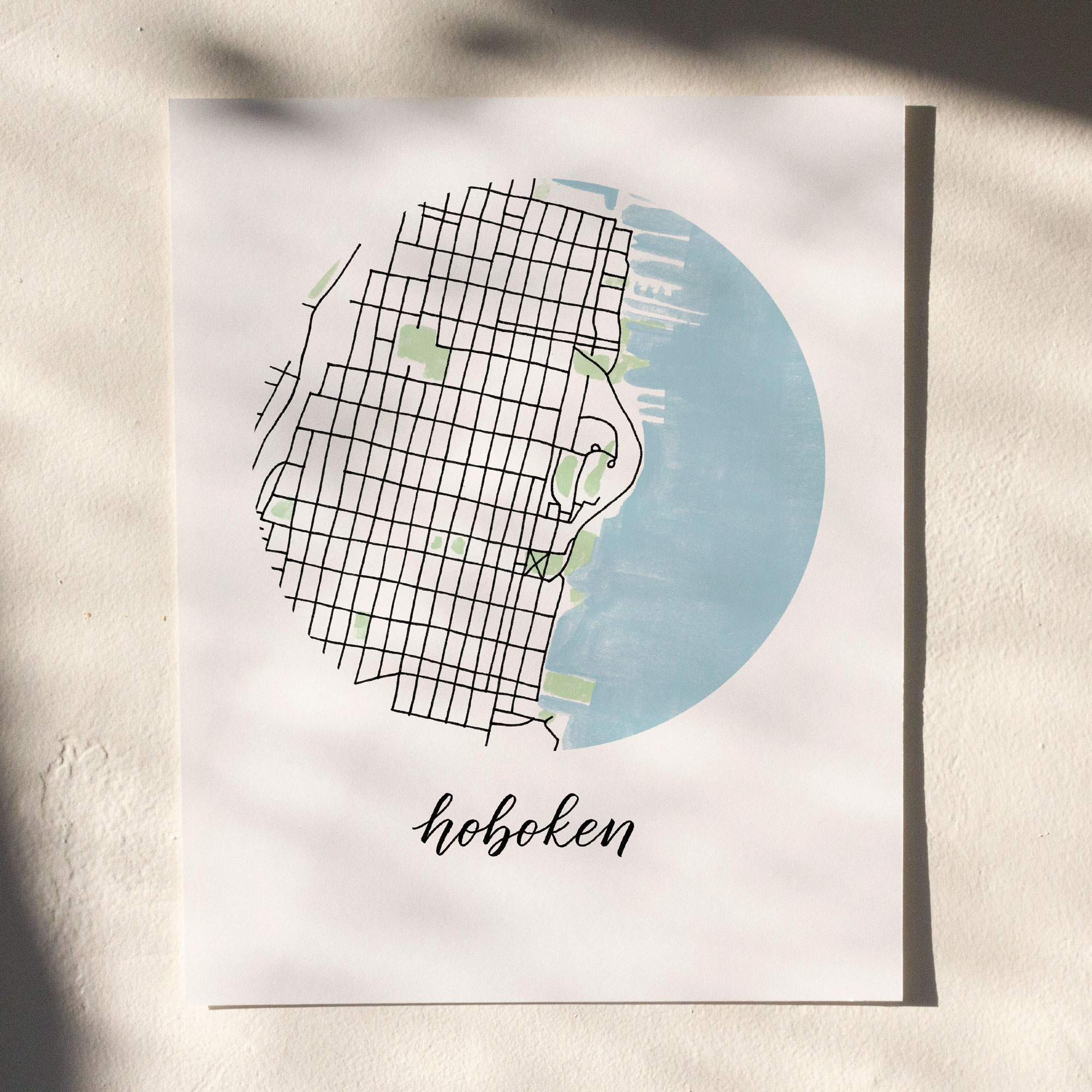 Hoboken Map Print hanging on white wall with leaf shadows across the image