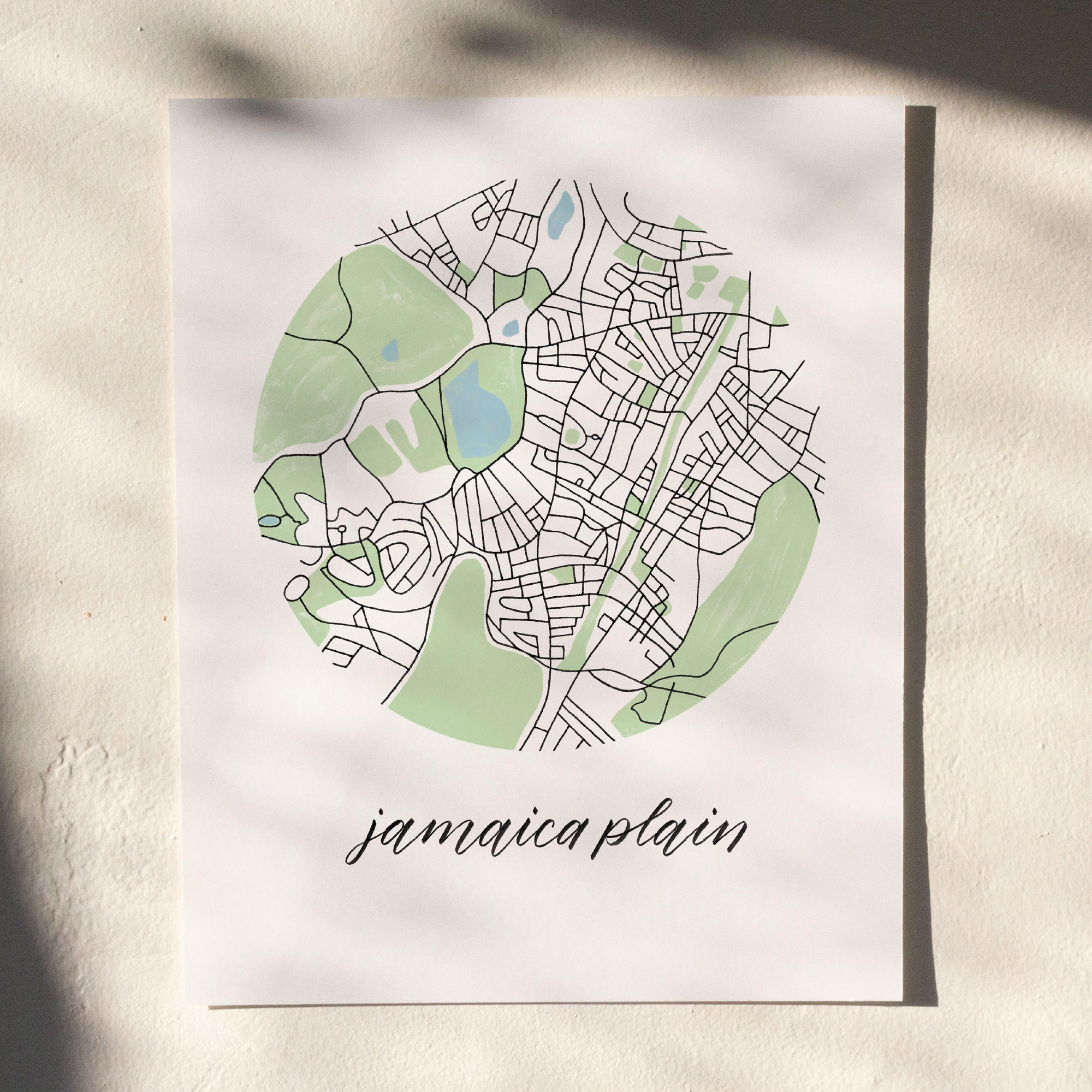 Jamaica Plain, Boston Map Print hanging on white wall with leaf shadows across the image
