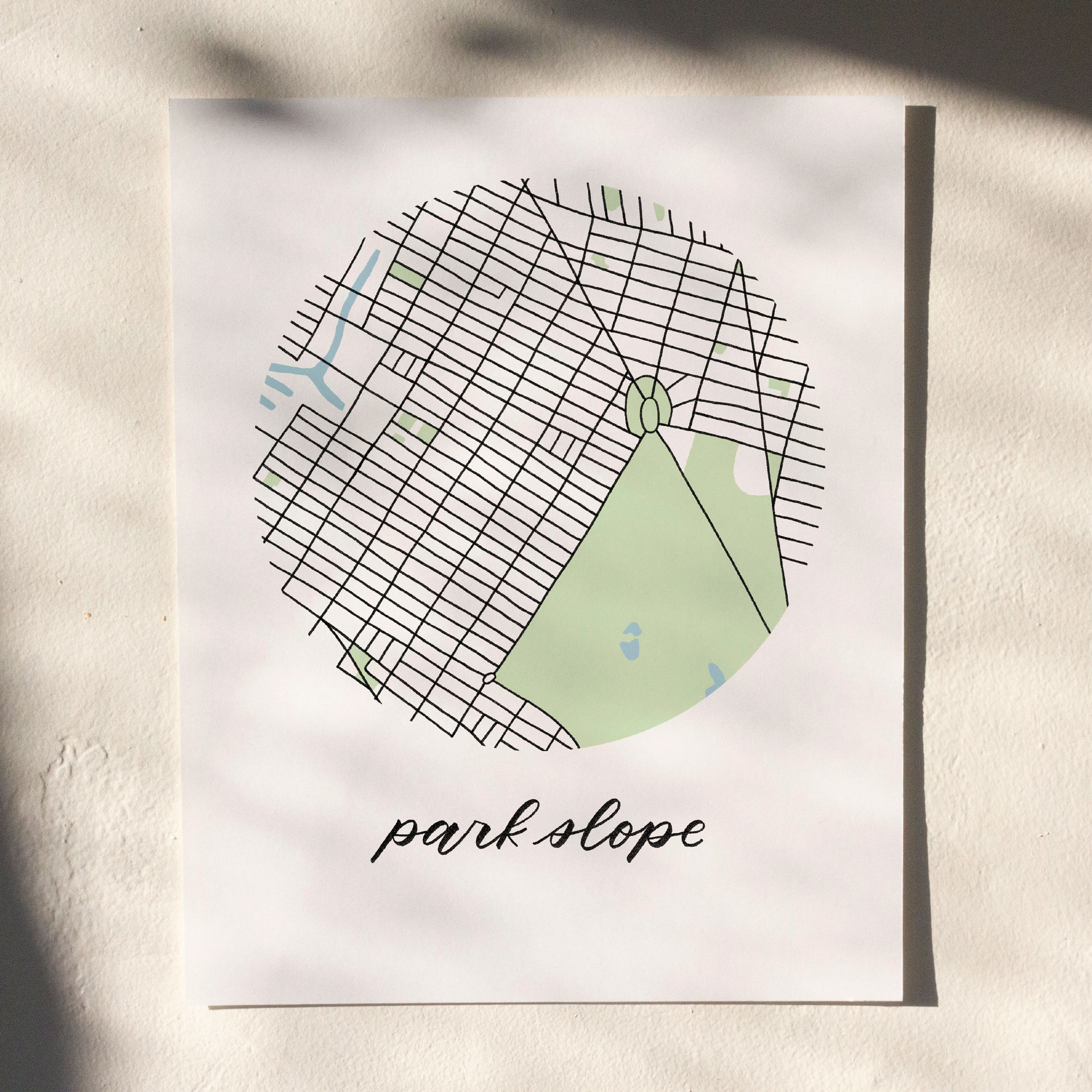 Park Slope, Brooklyn Map Print hanging on white wall with leaf shadows across the image