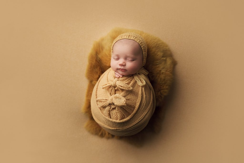 affordable newborn photographer BC newborn wrapped in yellow with bows