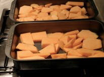 Placing pumpkin pieces into roasting tin, in 1 layer!