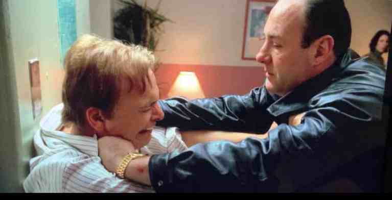 Tony Soprano is holding Ralph against a wall at the hospital as he cries over his son.