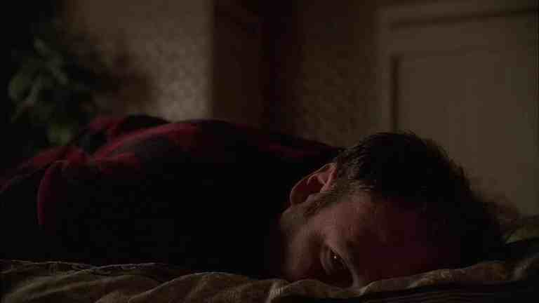 Tony is laying down on his bed while having hallucinations about seeing an imaginary woman named Isabella.